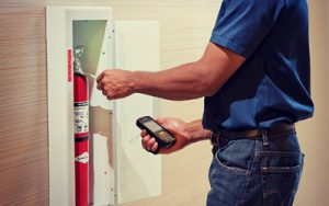 man servicing fire extinguisher